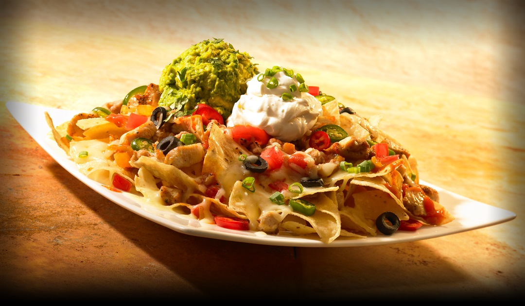 Nachos with cheese, olives, sour cream, and gauc