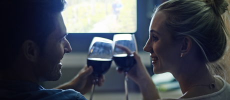 Man and woman clinking glasses of wine in front of a movie screen