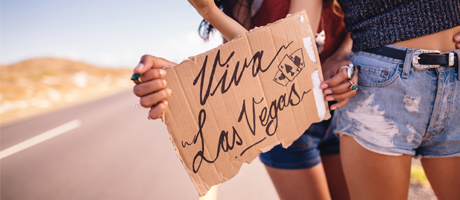 "Two women hitchhiking on a desert road, holding a piece of cardboard that says ""Viva Las Vegas"""