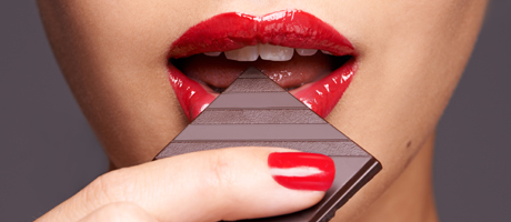 Woman wearing red lipstick and red fingernail polish, eating a piece of chocolate
