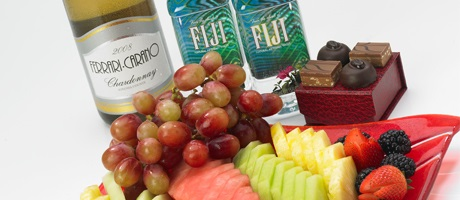 Hotel amenities including fresh fruit, chocolates, bottled water, and wine